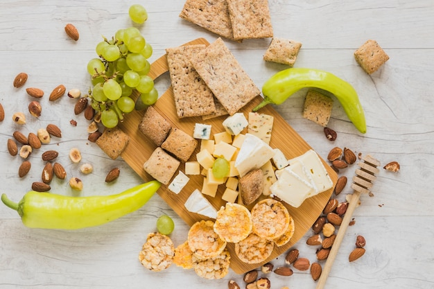 Green peppers, grapes, dried fruits, crackers, crisp bread and cheese blocks on wooden desk Free Photo