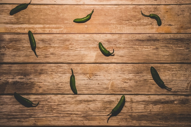 Green peppers on wood background Premium Photo