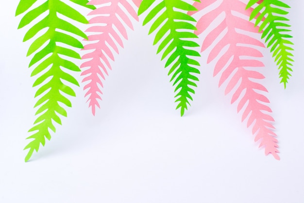 Green and pink tropical paper palm leaves on white surface Premium Photo