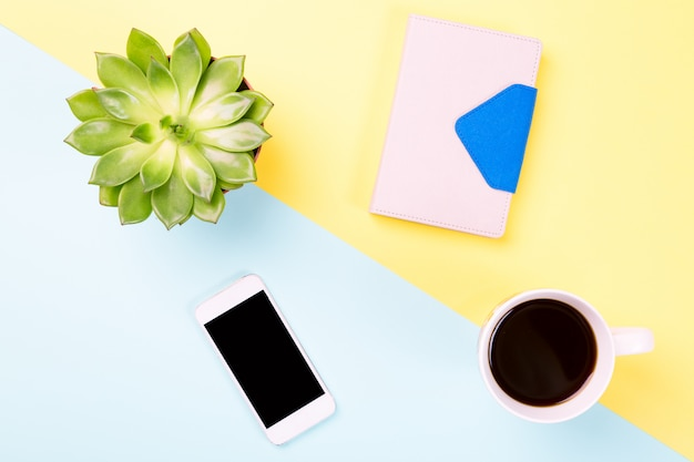 Green plant in a pot, cup of coffee, notebook and modern mobile phone on blue and yellow pastel surface. Premium Photo