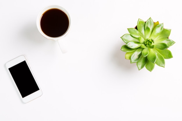 Green plant in a pot with cup of coffee and modern mobile phone and on white table. Premium Photo