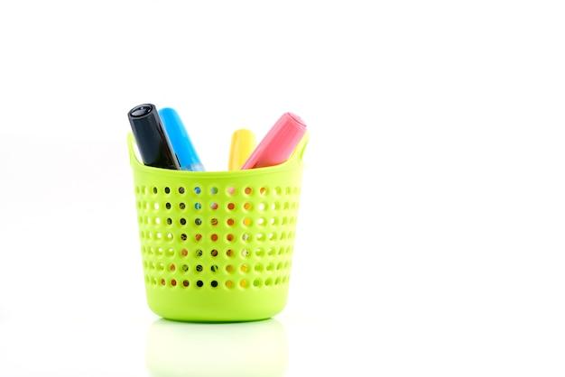 カラフルなペンや文房具を白で隔離される緑のプラスチックバスケット Premium写真