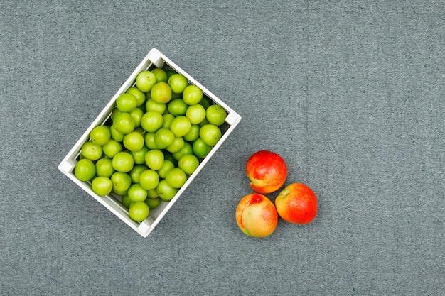 Зеленые сливы в миску белого прямоугольника со свежими персиками на серый. плоская планировка Бесплатные Фотографии