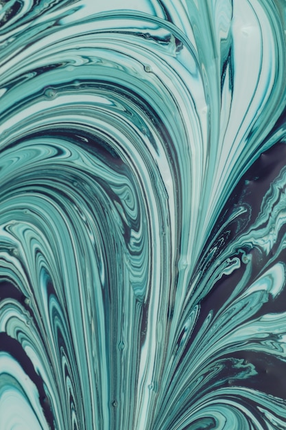Green pouring painting. beautiful abstract background. the process of mixing dark green and white paint. Premium Photo