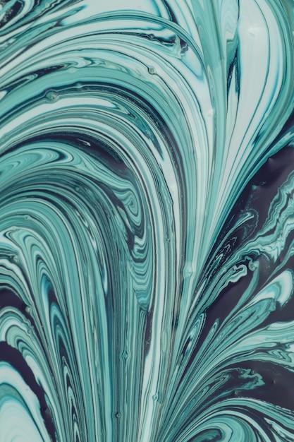Зеленая заливка картины. красивый абстрактный фон. процесс смешивания темно-зеленой и белой краски. Premium Фотографии