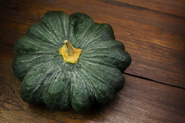 Green pumpkin on wood table image close up. Premium Photo