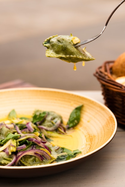 Green ravioli pasta with onion and basil leaves in plate Free Photo