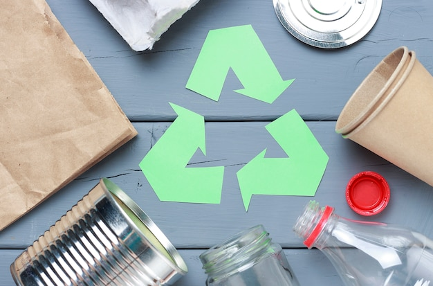 A green recycle garbage symbol and plastic, iron garbage on a gray Premium Photo