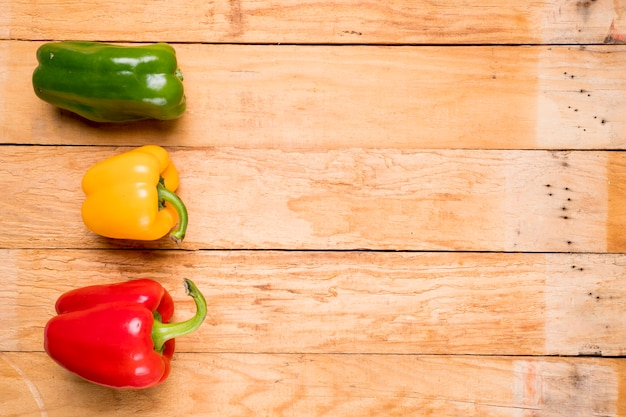 Green; red and yellow bell peppers on wooden plank Free Photo