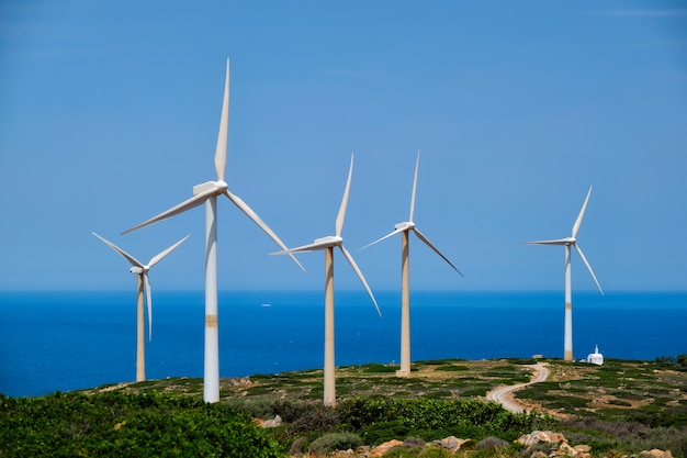 Green renewable alternative energy concept - wind generator turbines generating electricity. wind farm on crete island, greece with small white church Premium Photo