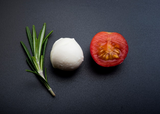 Green rosemary; half cheery tomato and mozzarella cheese over black surface Free Photo