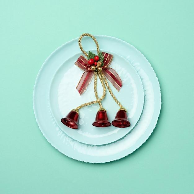 Зеленая круглая красная керамическая тарелка, праздничная сервировка стола на рождество и новый год Premium Фотографии