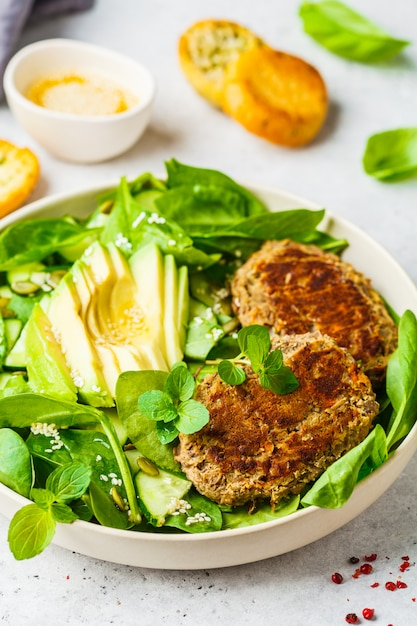 Green salad with avocado, cucumber and lentil cutlet in white plate. Premium Photo