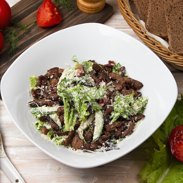 Green salad with brown mushrooms, chopped meat, lettuce and parmesan. Free Photo