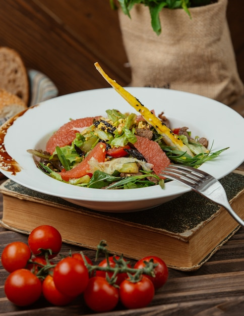 Green salad with pepperoni and galetta bread Free Photo