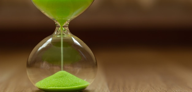 Green sand in an hourglass on a blurred background, close-up Premium Photo