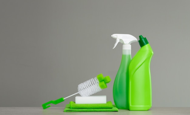 Green set of cleaning products and tools for spring cleaning. Premium Photo