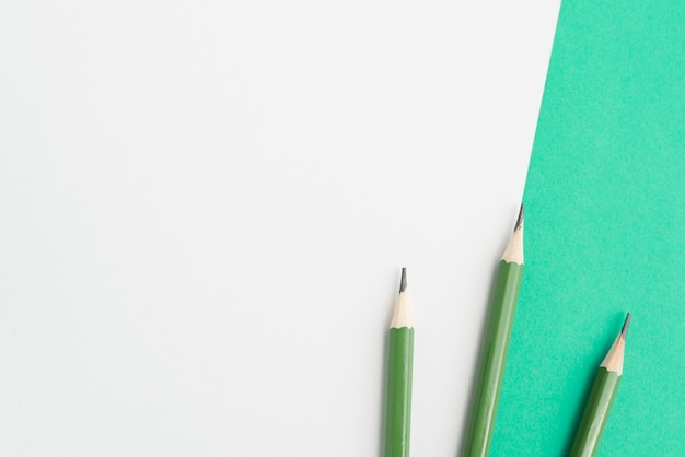 Green sharp pencils on dual background Free Photo