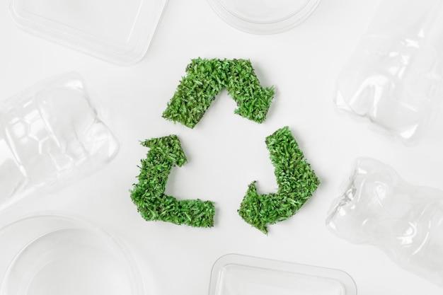 Зеленый знак - символ утилизации отходов травы на белом фоне. понятие экология Premium Фотографии