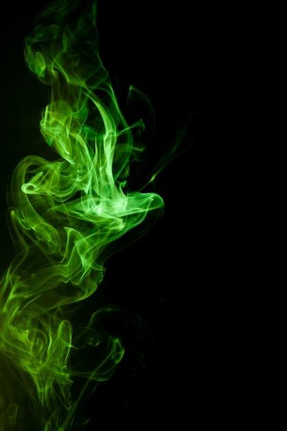 Green smoke motion on black background. Premium Photo