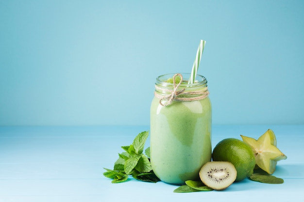 Green smoothie jar with blue background Free Photo