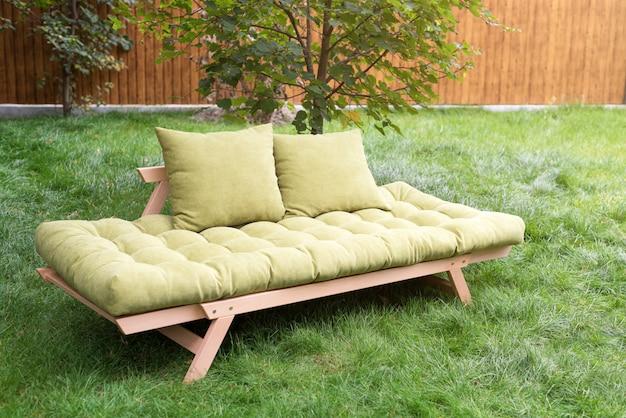 Green sofa in the yard outdoors. outdoor furniture in green garden patio. Premium Photo