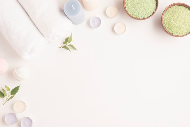 Green spa salt bowl with rolled up towel, candles and spa bomb on white backdrop Free Photo