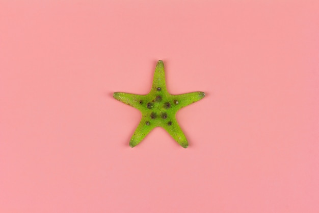 Green starfish on pink background close-up, top view flat lay Premium Photo