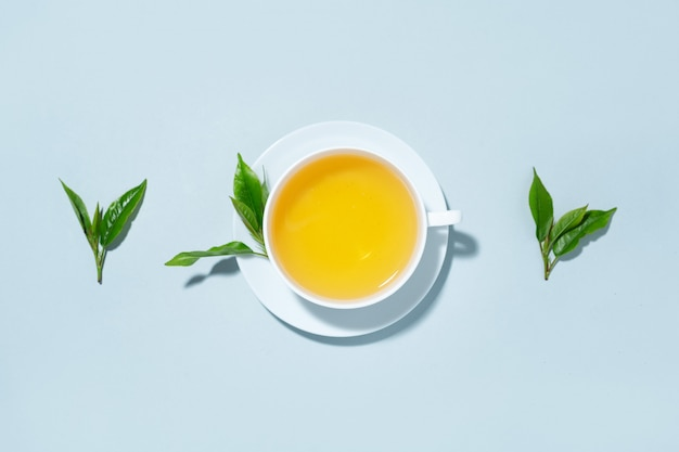 Green tea brewed in cup with tea leaves on blue pastel background. top view. Free Photo