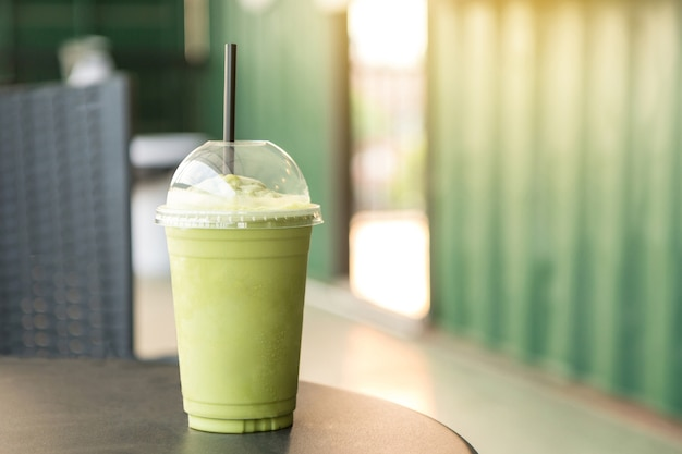 Green tea matcha smoothies in plastic cup in the coffee shop Premium Photo