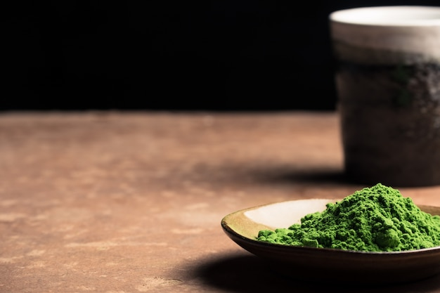 Green tea powder with ceramic cup on the table, black background. free space for text Premium Photo