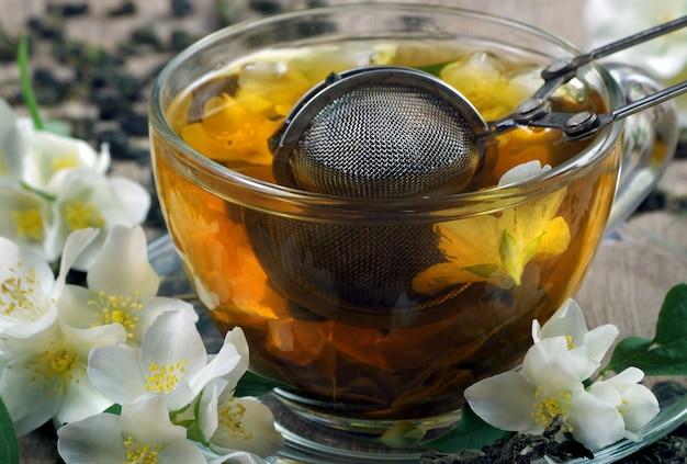 Зеленый чай с жасмином. сухие листья зеленого чая с цветами жасмина и чашка чая на деревянном столе. Premium Фотографии