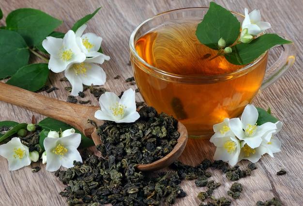 Зеленый чай с жасмином. сухие листья зеленого чая с цветами жасмина в деревянной ложке и чашкой чая на деревянном столе Premium Фотографии
