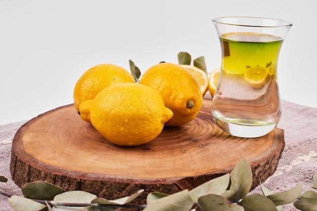 木製の丸いボードにレモンと緑茶。 無料写真