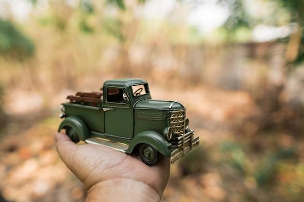 Green toy pickup truck on hand Premium Photo