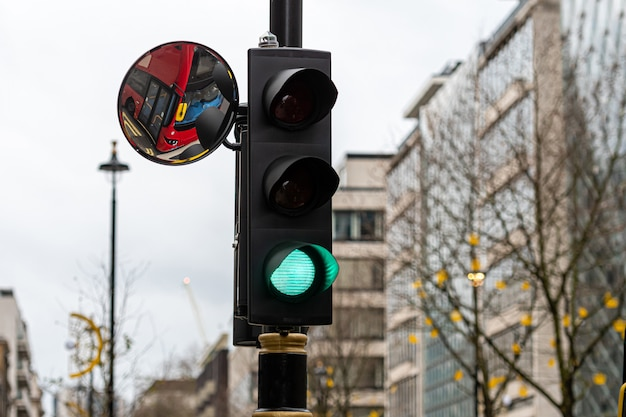 Green traffic light signal and traffic convex mirror with the reflection of the red bus Premium Photo