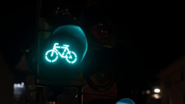 Semaforo verde con il logo della bicicletta su di esso di notte a bucarest, in romania Foto Gratuite