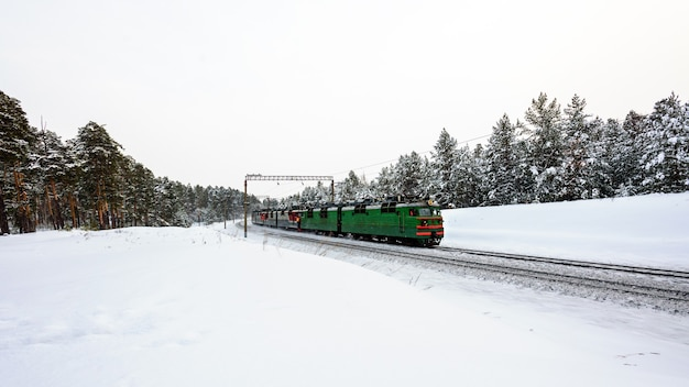 녹색 기차는 기차 개념으로 여행하는 겨울 숲을 통과합니다. 프리미엄 사진