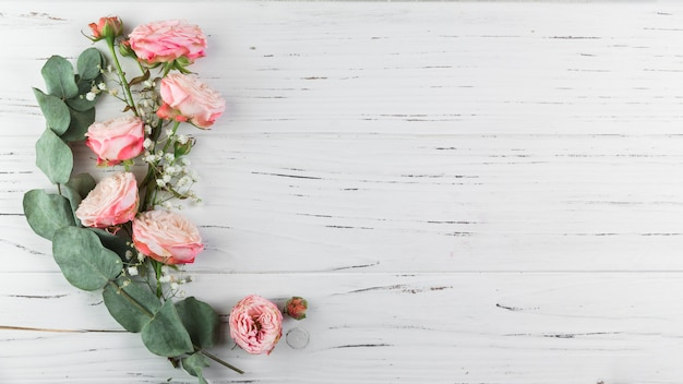 Green twig; pink roses and white gypsophila on white wooden textured background Free Photo