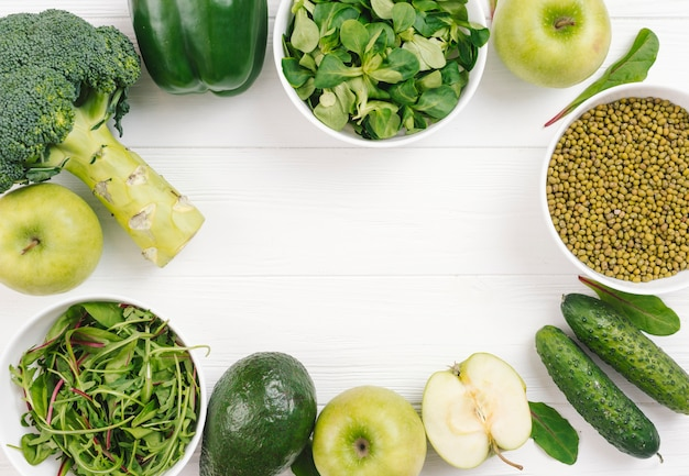 Green vegetables arranged in circular shape on white plank board Free Photo