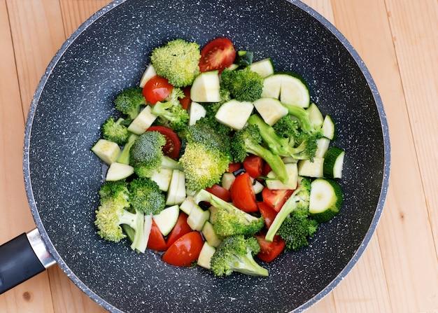 Зеленые овощи, брокколи, кабачки, помидоры в сковороде voc Premium Фотографии