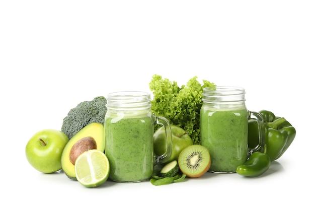 Зеленые овощи, фрукты и банка смузи, изолированные на белом фоне Premium Фотографии