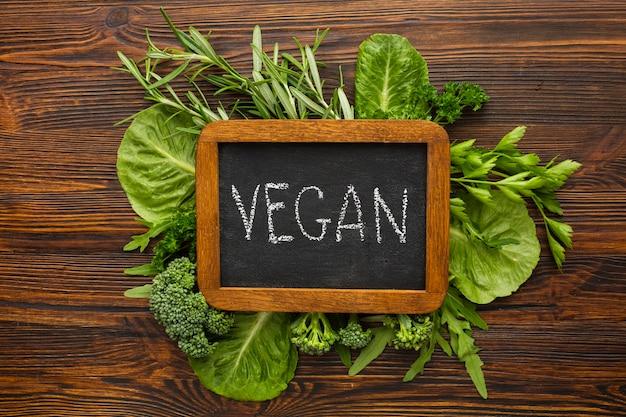 Green veggies with vegan lettering on chalkboard Free Photo