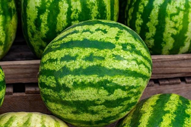 Зеленые арбузы на рыночной скамейке или прилавке. Premium Фотографии