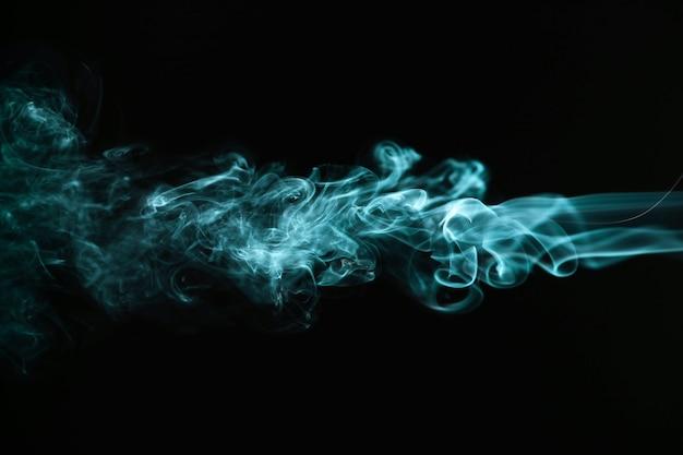 Green wavy smoke on black background Free Photo