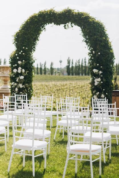 Зеленая арка свадебной церемонии и белые стулья Бесплатные Фотографии