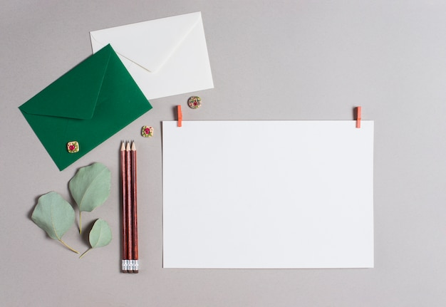 Green and white envelope; pencils and blank paper on gray backdrop Free Photo