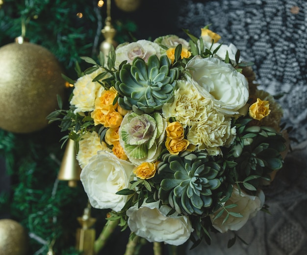 Green yellow bouquet with golden christmas ball. Free Photo