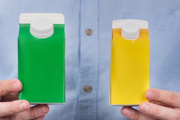 Green and yellow cartones milk or juice in mens hands. copy space, mock up Premium Photo