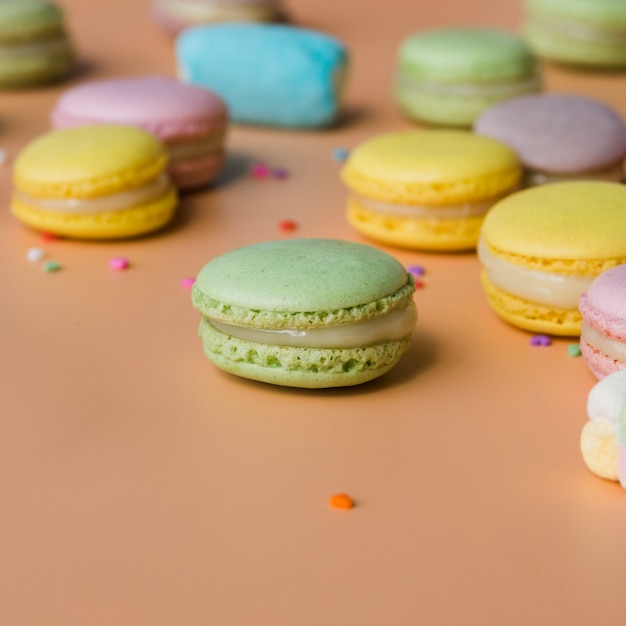 Green; yellow; pink; and blue macaroons on colored background Free Photo